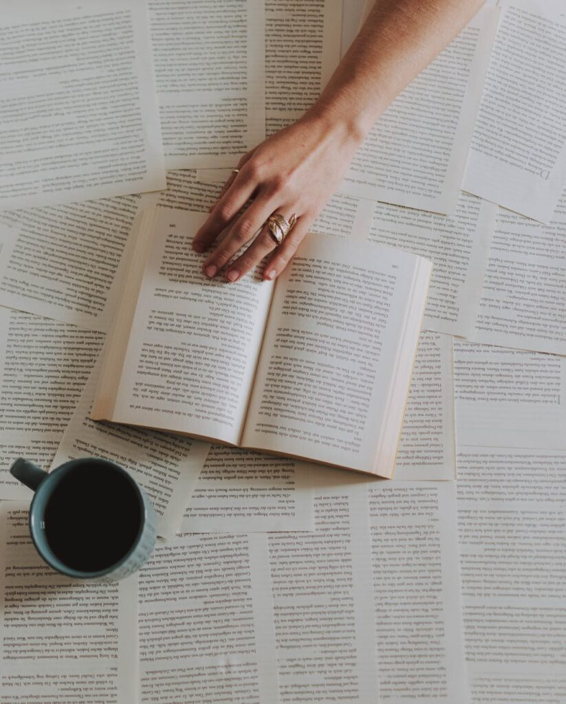flat lay photography of an open book beside coffee mug