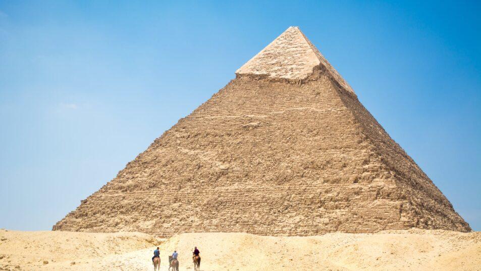 people riding a camel near pyramid under blue sky