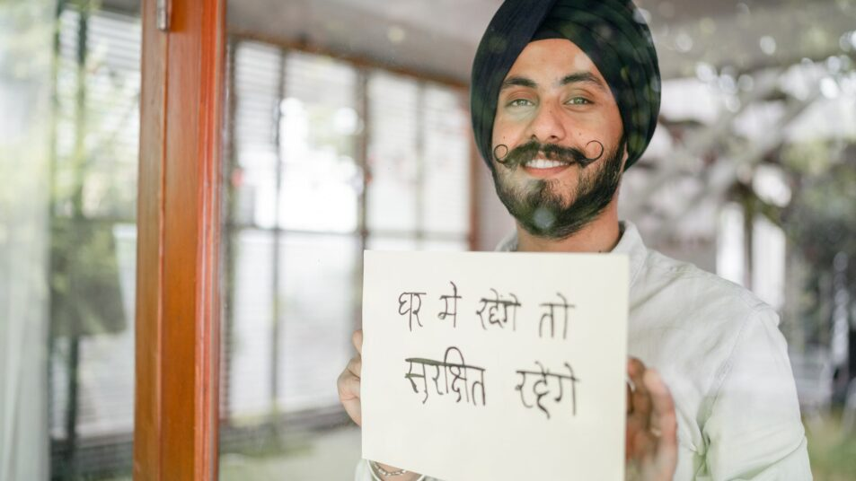 content indian guy showing paper with hindi inscription